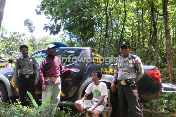 Tersangka Saridi (kaos putih) duduk dikawal anggota Polsek Sidoharjo setelah berhasil diamankan di pekarangan dekat rumahnya