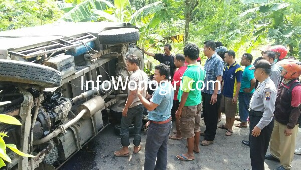 warga menyaksikan truk box yang terguling dan menimpa pemotor