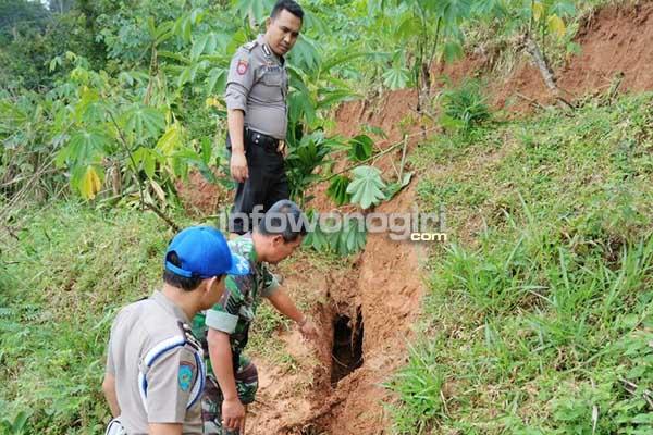 Anggota TNI dan Polri Jatipurno meninjau lokasi tanah tebing retak menganga di wilayah Jatipurno Wonogiri, Selasa (28/2)